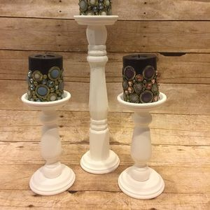Set of 3 white candlesticks.
